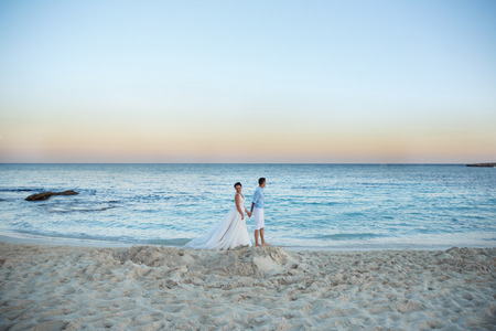 Foto de Beautiful smiling young bride and groom walking on the beach, kissing and having fun, wedding ceremony near the rocks and sea. Wedding ceremony on coast of Cyprus - Imagen libre de derechos