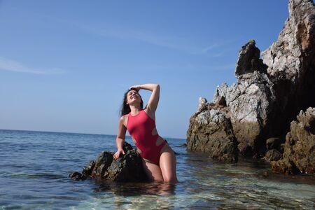 Photo pour Girl on the rocky beach of the azure sea of Thailand - image libre de droit