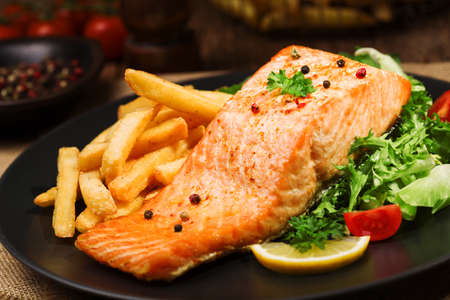 Photo pour Baked salmon served with french fries and fresh vegetables. - image libre de droit