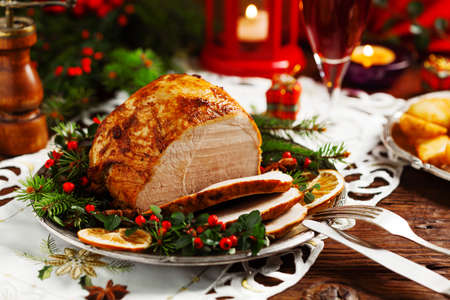Photo pour Christmas baked ham, served on the old plate. Spruce twigs all around. Front view. - image libre de droit