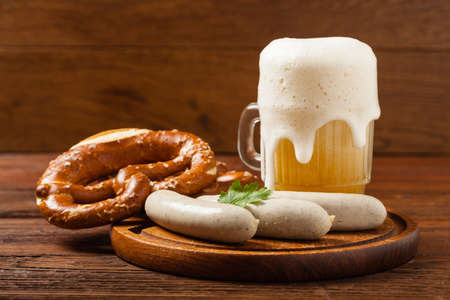 Boiled white sausages, served with beer and pretzels. Perfect for Octoberfest. Natural wooden background. Front view.
