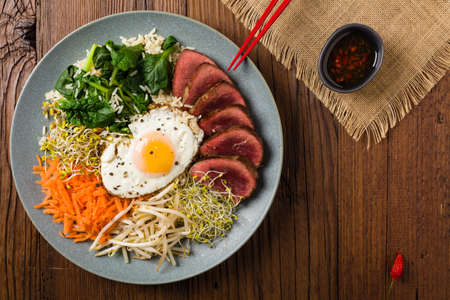 Photo pour Korean beef with sprouts, spinach and fried egg. Top view. - image libre de droit