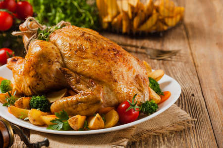 Photo pour Roasted chicken. Served on a plate with vegetables and baked potatoes. - image libre de droit