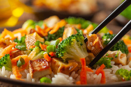 Photo pour Tofu with rice and vegetables. Served on brown plate. Close up. - image libre de droit