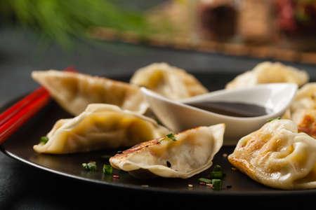 Photo pour Original Japanese dumplings Gyoza with chicken and vegetables. Front view. Dark blue backgrund. - image libre de droit