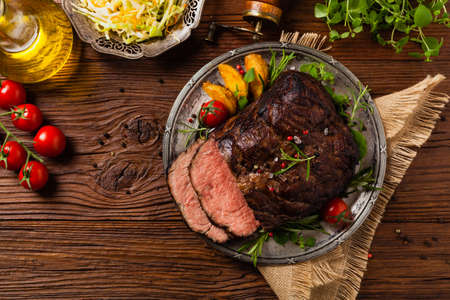 Photo pour Roasted brisket. Rustic style, natural wooden background. Dark style. Top view. Flat lay. - image libre de droit