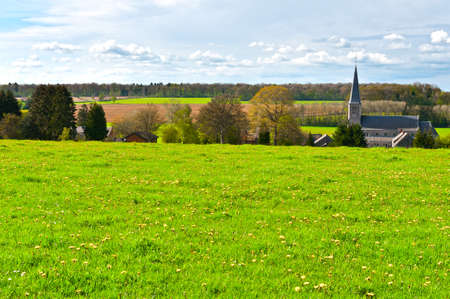 Photo for Green Meadow on the Background of the Village Church in Belgium - Royalty Free Image
