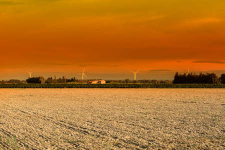 Vineyard in France early in the morning. French landscape at sunrise, hills, fields, pasture and sunlight. Modern wind turbines producing energy
