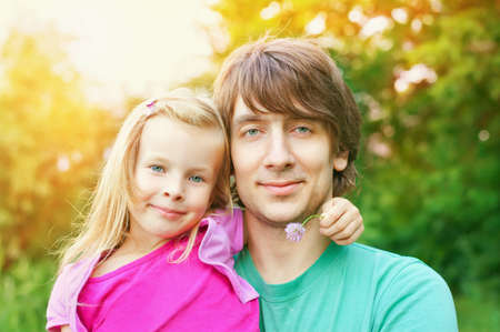 father and daughter.Young man and beautiful little girl outdoors in park  in summer