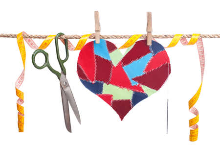 fabric scraps heart and sewing accessories hanging on the clothesline. Isolated on white. Valentine's Day