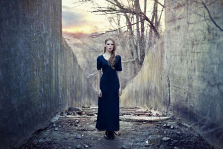 beautiful lonely girl  in long dress near gloomy tunnel on sunset