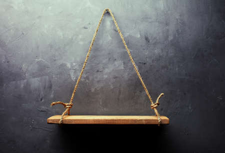 Empty old wood shelf hanging on rope on textured wall background