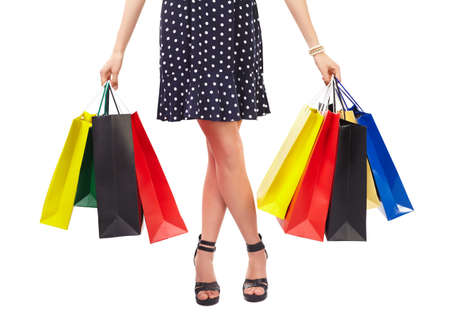 Waist-down view of woman holding colorful shopping bags isolated on white background