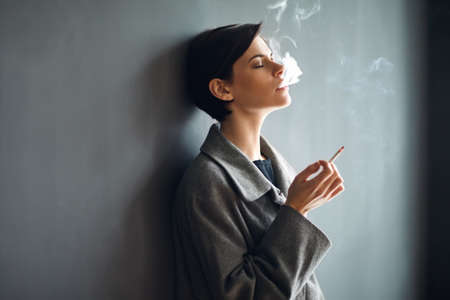 Portrait of fashionable woman smoking a cigarette on dark backgroundの写真素材