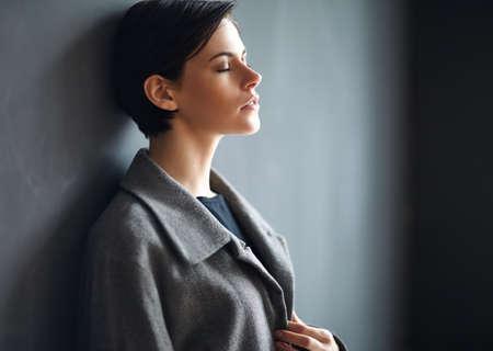 Photo pour Portrait of tired beautiful woman on dark background - image libre de droit