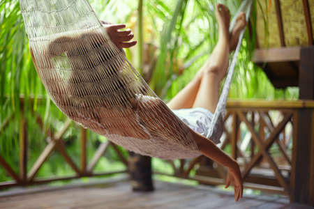 Young beautiful woman relaxing in hammock in a tropical resort.back view