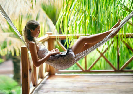 Photo for Young beautiful woman lying in a hammock with laptop in a tropical resort - Royalty Free Image