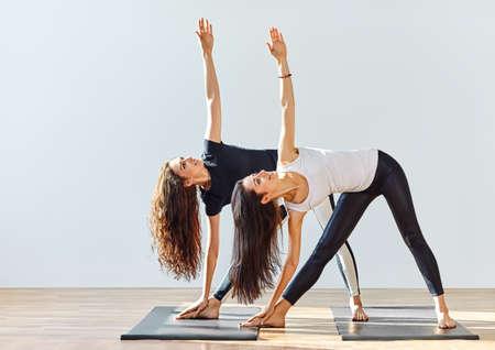 Foto de Two young women doing yoga asana extended triangle pose. Trikonasana - Imagen libre de derechos