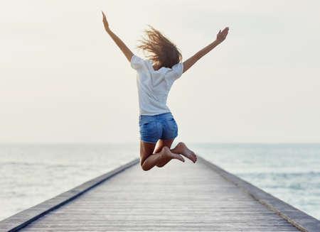 Foto de Back view of jumping girl on the pier. Freedom concept - Imagen libre de derechos