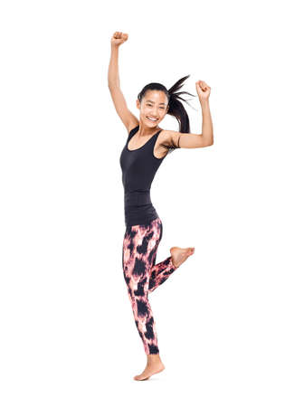 Cheerful smiling young Asian woman in sportswear dancing. Isolated portrait in full growth of female athlete in motion with her arms raised, standing on one leg and waving hair