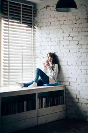 Woman drinking hot coffee sitting on window sill at home. Relax concept