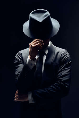 Foto de Man in suit hiding face behind his hat isolated on dark background. secret and incognito concept                  - Imagen libre de derechos