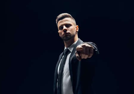 Photo pour Serious handsome man in black suit pointing his finger to you and camera isolated on dark background. Choice concept - image libre de droit
