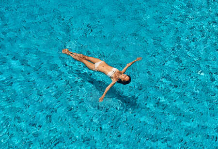 Photo pour Top view of young slim woman in white bikini relax and floating in infinity swimming pool - image libre de droit