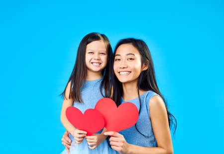 Foto de Smiling little girl and her mom holding paper heart on blue background. Happy family love concept - Imagen libre de derechos