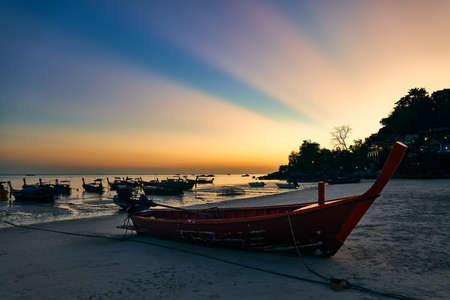 Photo pour Fantastic sunset with sun light rays on tropical island and boats on beach - image libre de droit