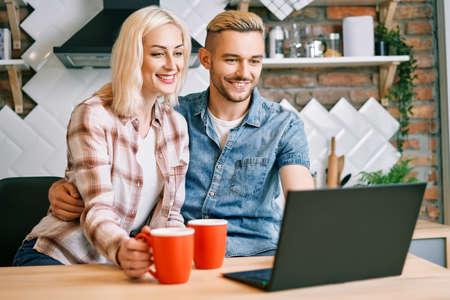 Foto de Happy couple drink coffee and using laptop relax together at their kitchen - Imagen libre de derechos