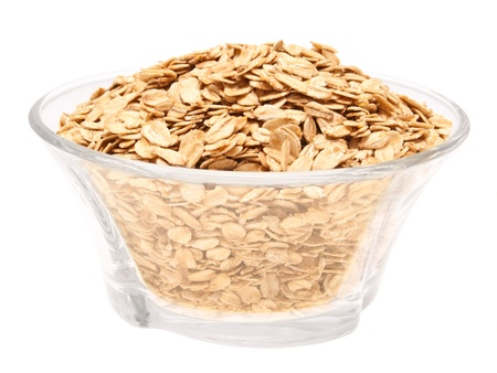 Rolled oats in a glass bowl - top view  On a white background