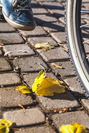Leg in dark blue leather sneaker on a bicycle pedal. Next to the square of sidewalk tile is yellow fallen leaf