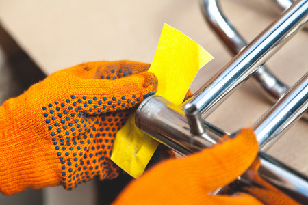 Photo for Grinding of a stainless heated towel rail. Hands in orange gloves clean out the metal structure with sandpaper  - Royalty Free Image