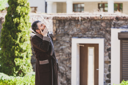 Summer morning in the courtyard. A man with a beard in a brown robe sweetly yawns into the courtyard of the estate in the early morning