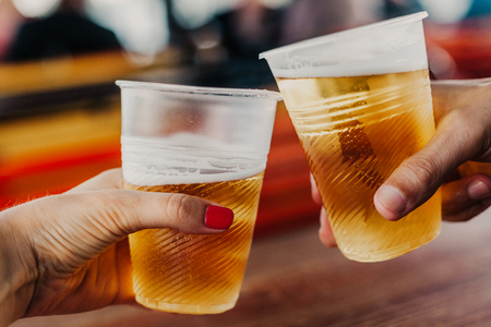 Photo pour Beer appointment. A hand with a woman with a manicure holds a plastic glass with beer. The second glass in the man's hand - image libre de droit