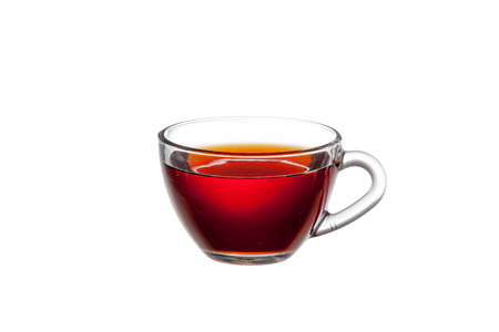 Transparent glass cup with brown tea on a white background close-up.