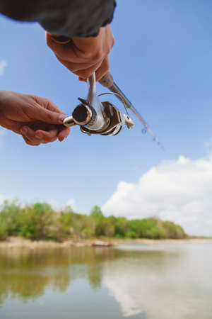 Photo pour Fisherman holding a spinning rod with a reel against a background of white clouds against a blue sky - image libre de droit