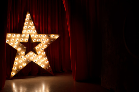 Photo pour Photo of golden star with light bulbs on red velvet curtain on stage - image libre de droit