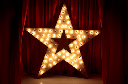 Photo for Photo of golden star with light bulbs on red velvet curtain on stage - Royalty Free Image
