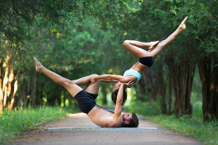 Foto de Acro yoga, two sporty people practice yoga in pair, couple doing stretching exercise in the garden - Imagen libre de derechos
