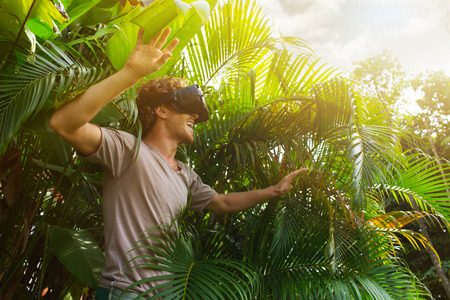 Photo pour man in gray T-shirt, virtual reality 3D headset and exploring the play on a background of nature jungle - image libre de droit