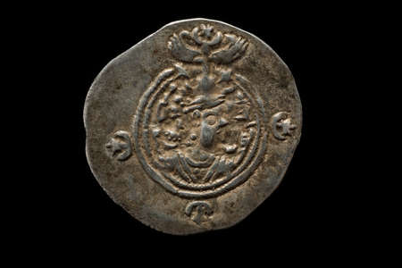 Ancient silver Sassanian coin isolated on black, irregular circle shape