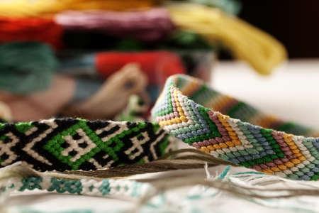 Foto de Bright friendship bracelets on a white table with heap of colored threads - Imagen libre de derechos