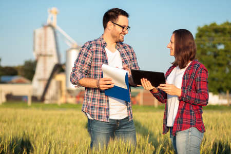Photo pour Two happy young male and female farmers or agronomists inspecting a wheat field before the harvest. Checking data on a tablet and clipboard. Organic farming and healthy food production. - image libre de droit