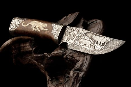 Details of elaborate wildlife and decorative designs on an ornamental hunting knife.