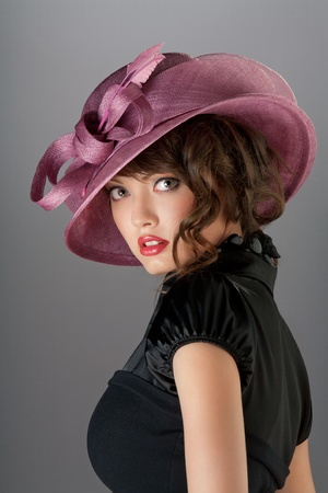 Independent look. A portrait of a sexy hot brunette with curly hair wearing a beautiful stylish hat.