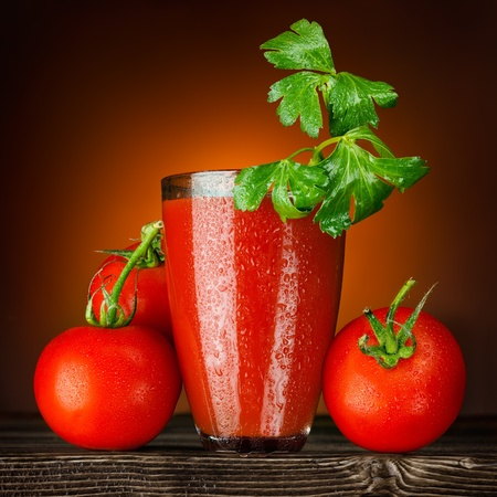 Foto de Red and wet! A wet glass of tomato juice decorated with parsley and ripe tomato bunch on a wooden table. - Imagen libre de derechos