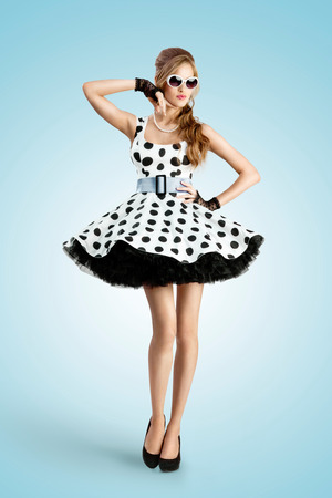 A vintage photo of a beautiful pin-up girl wearing a retro polka-dot dress and sunglasses.