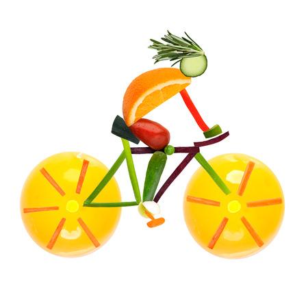 Foto de Fruits and vegetables in the shape of a male cyclist on a road bike  - Imagen libre de derechos